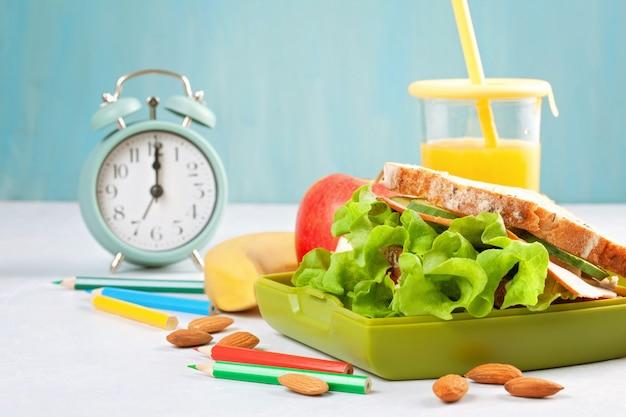 Sándwich fresco y saludable, jugo de manzana y naranja para el almuerzo de los estudiantes Foto Premium