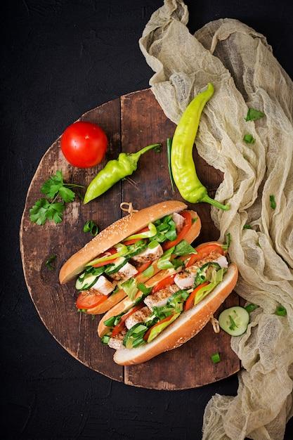 Sándwich grande con pechugas de pollo, tomate, pepino y hierbas. endecha plana. Foto Premium