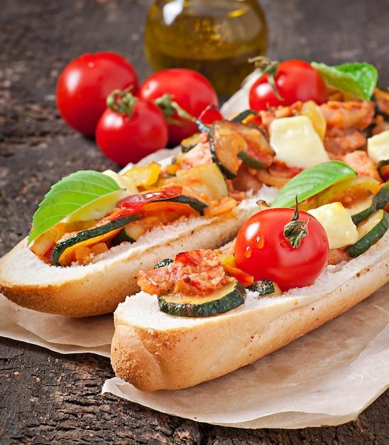 Sándwich grande con verduras asadas con queso y albahaca sobre superficie de madera vieja Foto gratis