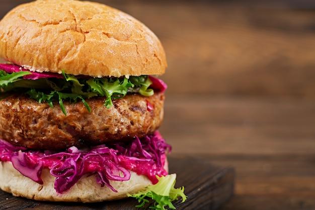 Sandwich de hamburguesa con jugosas hamburguesas, col lombarda y salsa rosa Foto gratis