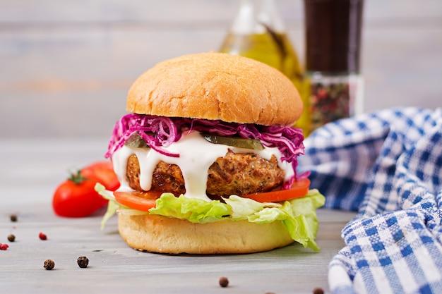Sandwich hamburguesa con jugosas hamburguesas, tomate y col lombarda Foto gratis