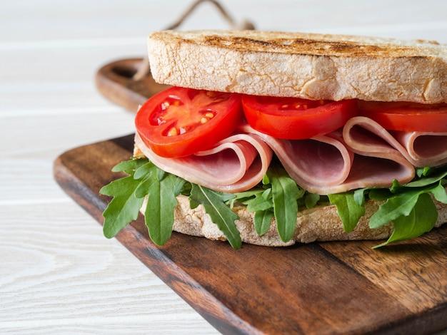 Sándwich de jamón, tomate y rúcula en rebanadas de pan tostado en una tabla para cortar madera en madera blanca. copyspace Foto Premium