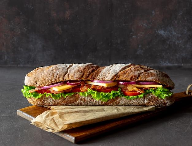 Sandwich de pan negro con ensalada, tocino, tomate, queso y cebolla. desayuno. comida rápida. Foto Premium