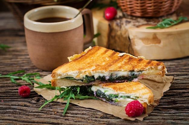 Sándwich de panini con queso y hojas de mostaza. cafe mañanero. desayuno de pueblo Foto Premium