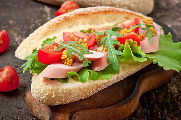 Sandwich con salchichas, lechuga, tomate y rúcula en la superficie de madera vieja Foto gratis