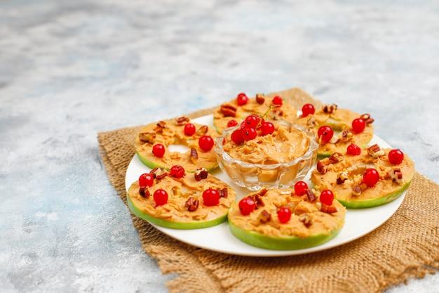 Sandwich saludable. rondas de manzana verde con mantequilla de maní y grosellas rojas y nueces pecanas sobre hormigón gris, vista superior Foto gratis