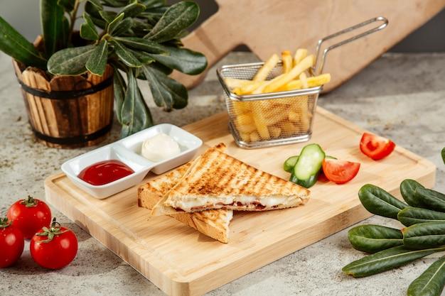Sandwich servido con papas fritas y vegetales Foto gratis