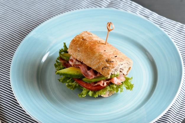 Sandwich con tocino y aguacate perforado con brochetas Foto Premium
