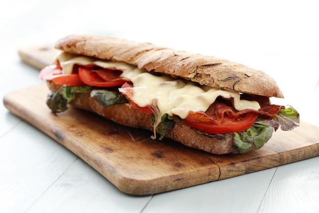 Sándwich de tocino y queso sobre tabla para cortar Foto gratis