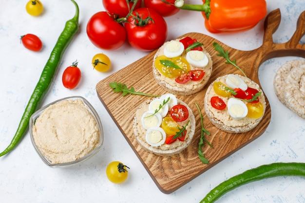 Sándwiches abiertos de pasteles de arroz con hummus, verduras y huevo de codorniz, desayuno o almuerzo saludable. Foto gratis