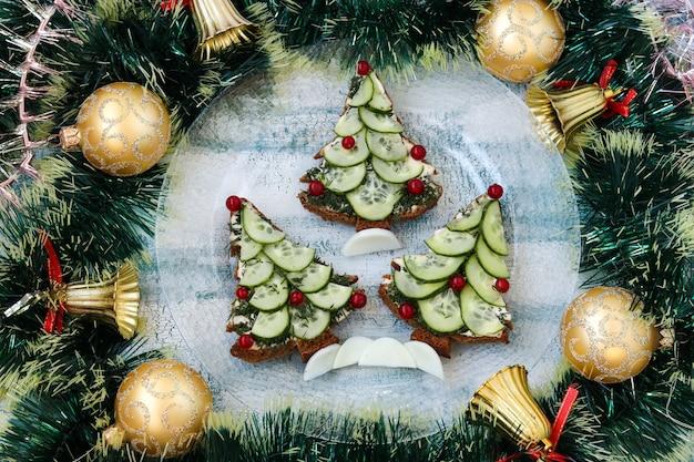 Sandwiches de año nuevo de pan negro, queso y pepinos en forma de árbol de navidad Foto Premium