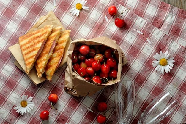 Sandwiches, cerezas y manzanilla sobre el mantel en una jaula - desayuno en la hierba Foto Premium