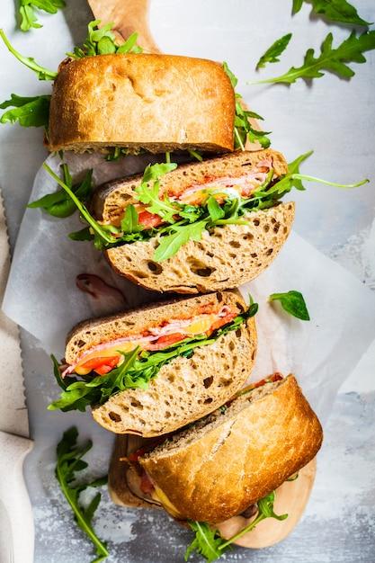 Sandwiches de chapata, jamón y verduras sobre una plancha de madera Foto Premium