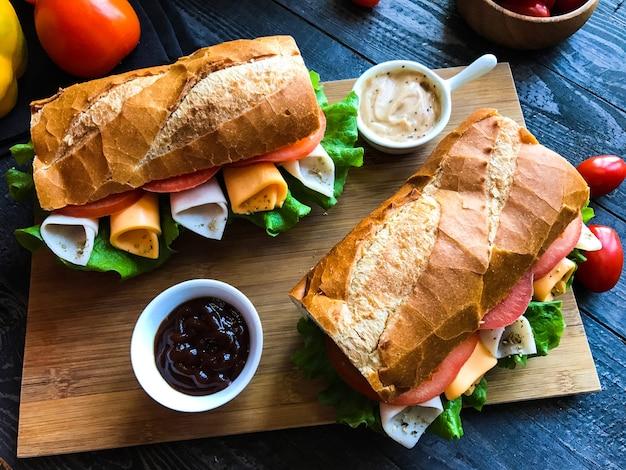 Sándwiches deliciosos y sabrosos con pavo, jamón, queso, tomates. Foto Premium