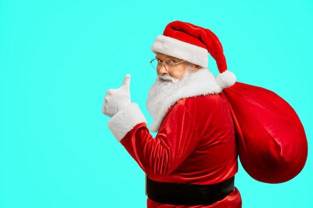 Santa claus con bolsa mostrando el pulgar hacia arriba. Foto gratis
