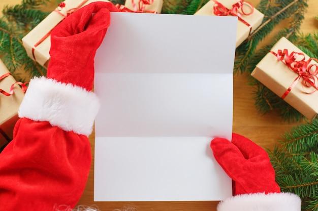 Santa claus con una lista de deseos vacía en sus manos Foto Premium