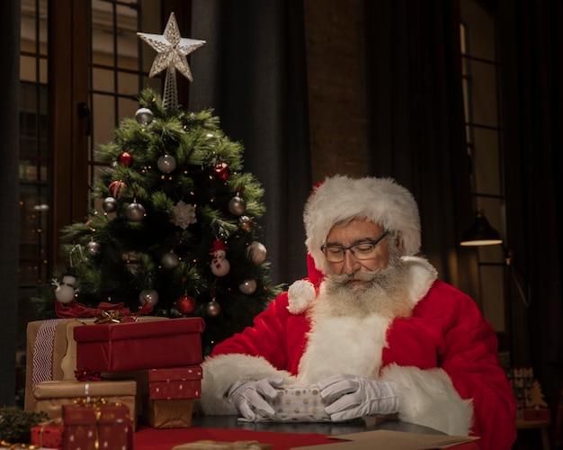 Santa claus preparando regalos de navidad Foto gratis