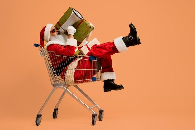 Santa gritando en megáfono mientras está sentado en el carrito de compras Foto Premium
