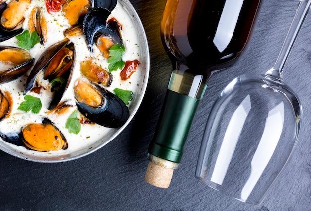 Sartén plana con mejillones en salsa blanca y botella de vino. Foto gratis
