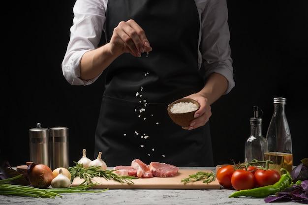 Sartén de sales de chef a la plancha. preparar carne fresca de res o de cerdo. Foto Premium