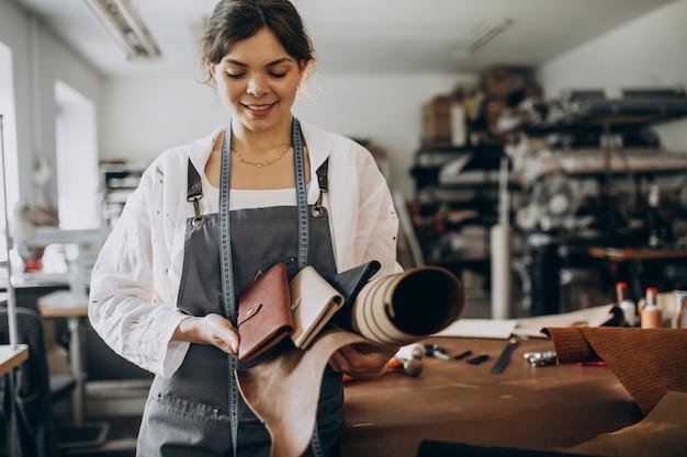 Sastre mujer trabajando en tela de cuero Foto gratis