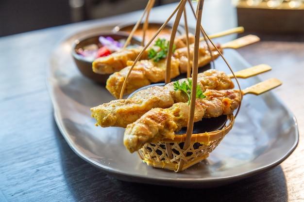 Satay de pollo o kebab de pollo en un plato con guarniciones y salsa tailandesa. Foto Premium