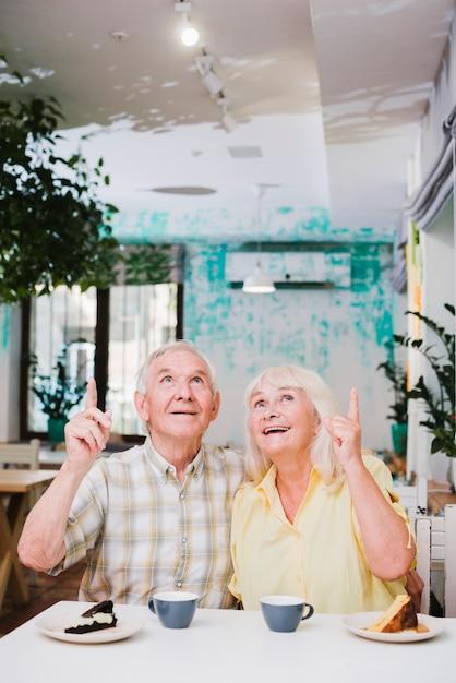 Satisfecho pareja de ancianos sentados en la cafetería Foto gratis
