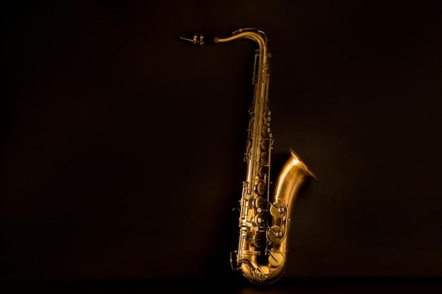 Saxofón saxofón tenor dorado en negro Foto Premium
