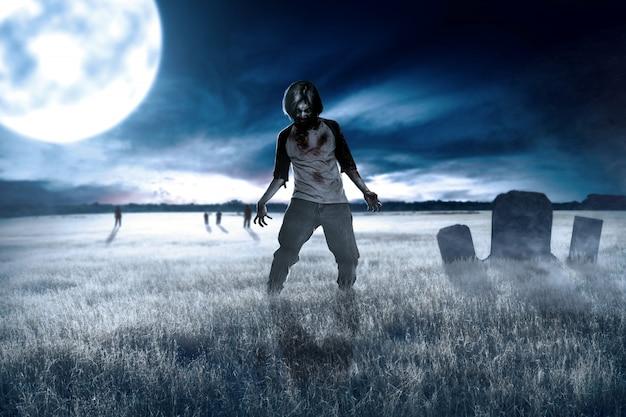 Scary zombies con sangre y heridas en su cuerpo caminando por el campo de hierba Foto Premium
