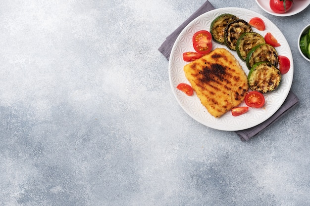 Schnitzel de pollo y calabacín cocinado a la parrilla. tomates frescos en un plato. listo deliciosa cena almuerzo. copia espacio Foto Premium