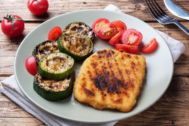 Schnitzel de pollo y calabacín cocinado a la parrilla. tomates frescos en un plato. listo deliciosa cena almuerzo. Foto Premium