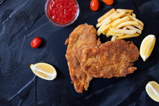 Schnitzel de pollo tradicional servido con papas fritas, salsa y limón. fondo negro Foto Premium