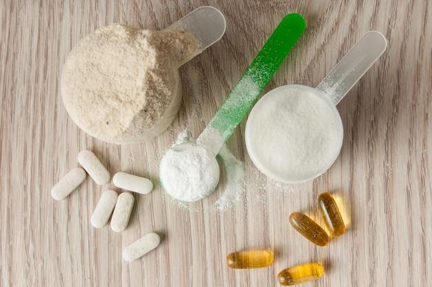 Scoop de proteína, bcaa y creatina, omega3 en pastillas. Foto Premium