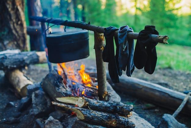 Secado de ropa mojada en la hoguera durante el campamento. calcetines de secado al fuego. caldero y hervidor de agua sobre la fogata. cocinar alimentos en la naturaleza. leña y ramas en fuego. descanso activo en el bosque. Foto Premium