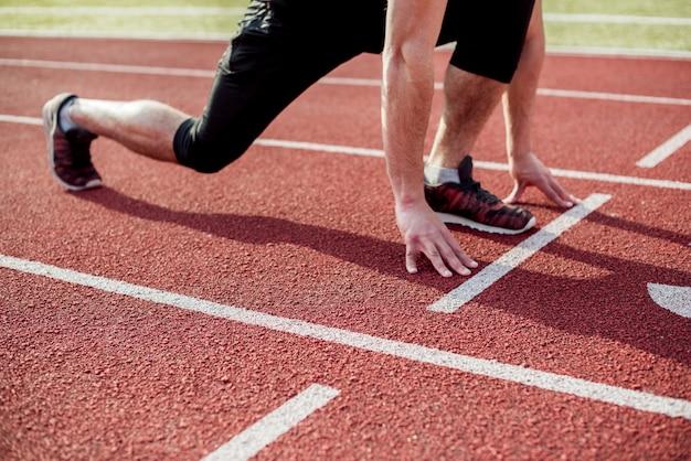 Sección baja de un atleta masculino en la línea de inicio de la pista de carreras Foto gratis