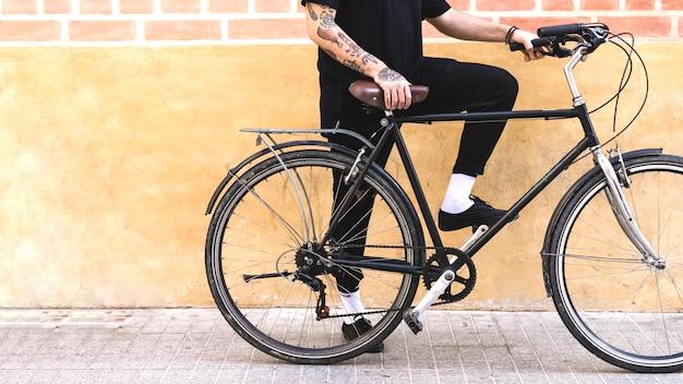 Sección baja de un hombre con bicicleta contra muro pintado y ladrillo. Foto gratis