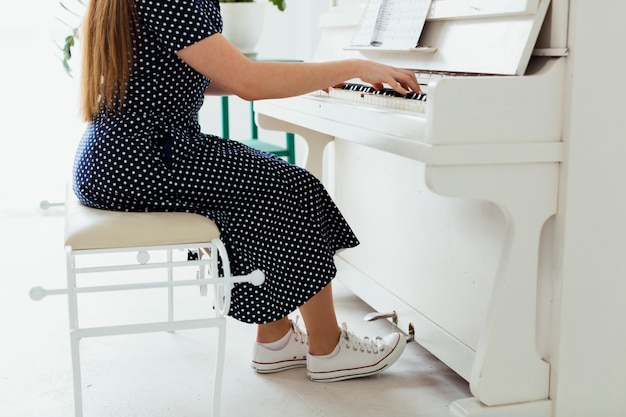 Sección baja de una mujer joven con zapatos de lona tocando el piano. Foto gratis