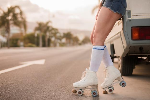 Sección baja de una mujer que lleva patín de ruedas que se inclina cerca de la camioneta en la carretera Foto gratis