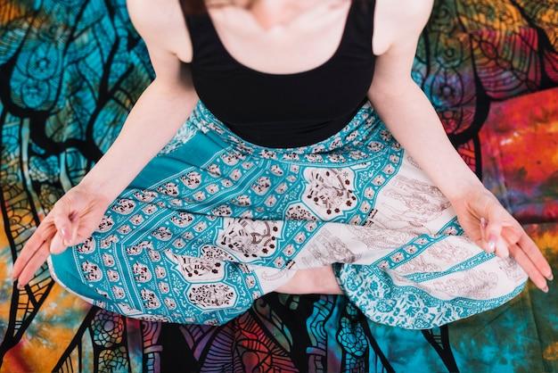 Sección baja de mujer sentada en postura de loto con gesto de mudra sobre una manta Foto gratis