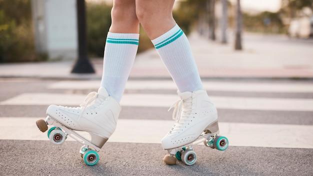 Sección baja de mujer vestida con patín vintage caminando en carretera Foto gratis