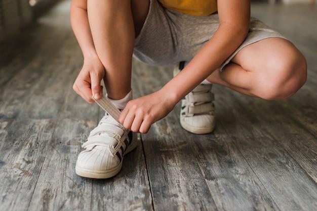 Sección baja de un niño que pone la correa del zapato en el piso de madera dura Foto gratis