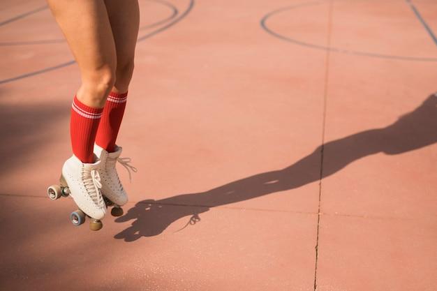Sección baja de patinadora femenina saltando en el aire en cancha Foto gratis