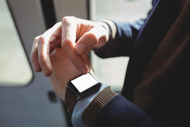 Sección intermedia del empresario con reloj inteligente mientras viaja Foto gratis