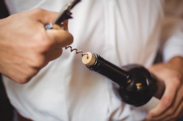 Sección media del barman abriendo una botella de vino Foto gratis