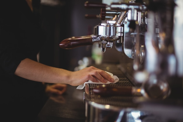 Sección media de la camarera limpiando la máquina de café espresso con una servilleta en el café Foto gratis