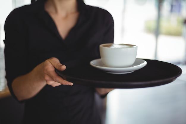 Sección media de camarera de pie con una taza de café Foto gratis
