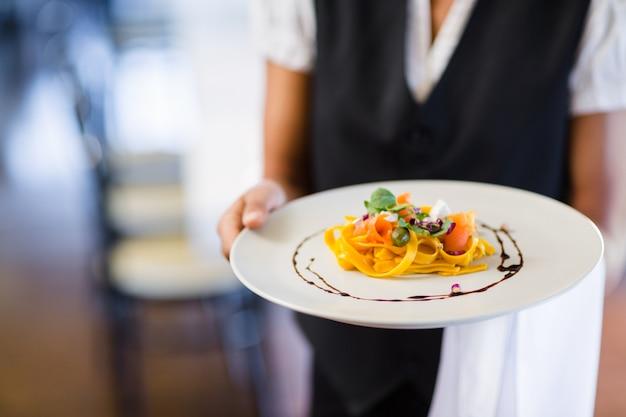 Sección media de camarera con plato Foto Premium