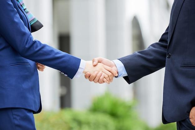Sección media de empresarios dándose la mano al aire libre Foto gratis