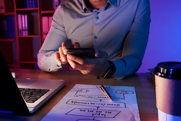 Sección media del hombre irreconocible tomando foto del plan de trabajo por teléfono Foto gratis