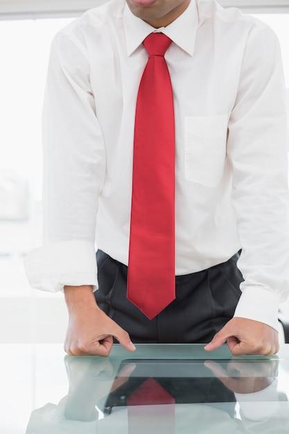 Sección media de un hombre de negocios bien vestido con los puños apretados en el escritorio Foto Premium